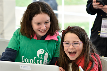 A woman in a CoderDojo t-shirt sits to the left of a laughing girl. Both are looking at a laptop.