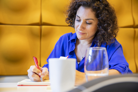 Woman taking notes with a coffee