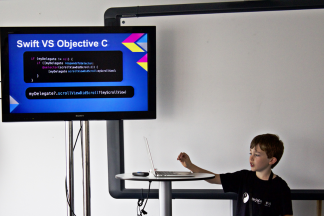 A boy in a CoderDojo t-shirt is delivering a lesson, with slides, on coding.