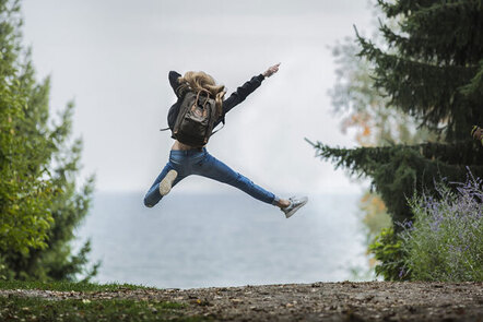 Image shows a person leaping into the air in celebration, whilst on a walk.