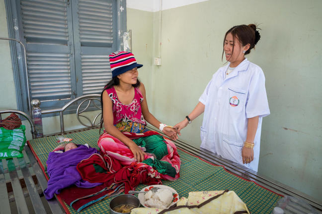 A female nurse holds the hand of a female patient sitting on a bed.