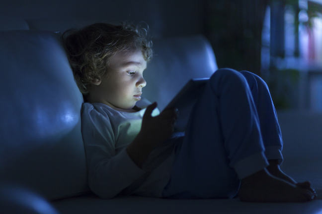 a young students on their ipad in the dark