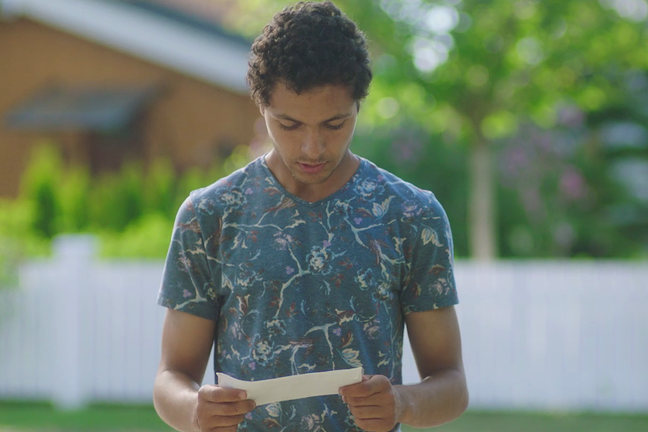 A teenage boy is standing outside looking down at a letter in his hand. He is frowning or looking worried. There is a white picket fence across the street behind him with trees behind the fence.