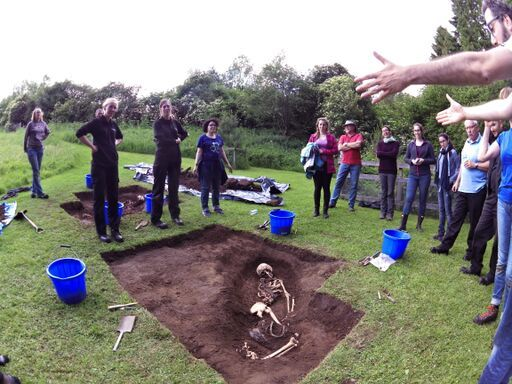 A forensic anthropologist explains a grave site with a body partially excavated to a group of students