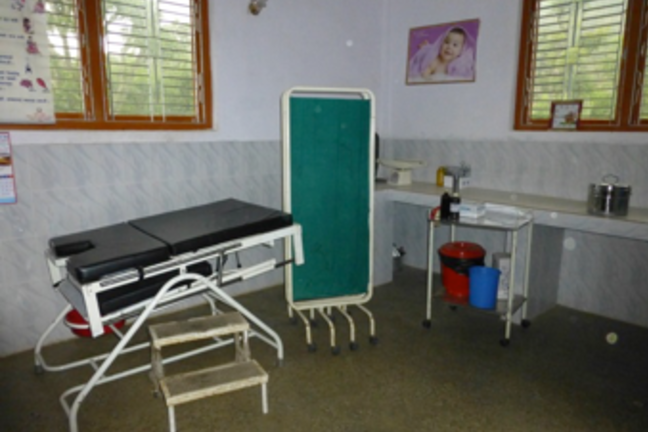 A health clinic with a bed and privacy screen is shown.