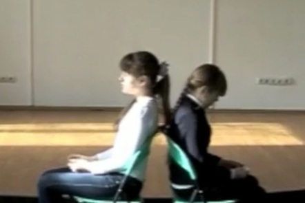 Two students sitting back to back