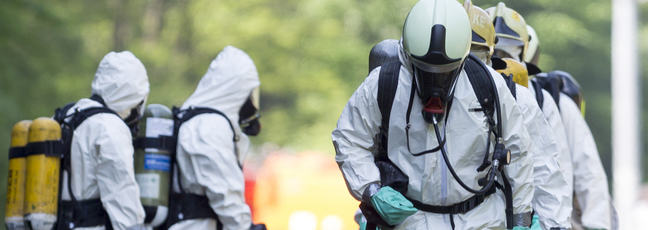 Men in hazmat suits and self-contained breathing apparatus