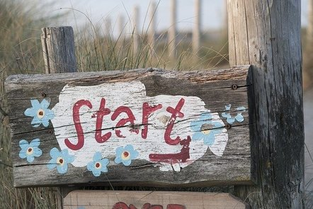 Photo of a wooden sign with the word Start hand painted on it.