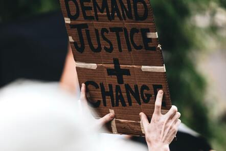 A cardboard sign reading we demand justice plus change