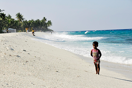 Child standing on beach in Maldives