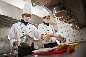 two male chefs cooking wearing hair nets, gloves and masks