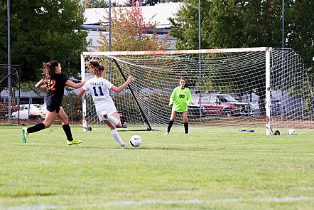 Three soccer players shooting at goal