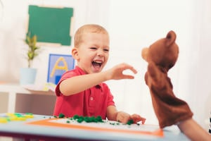 Boy interacting with puppet of a bear