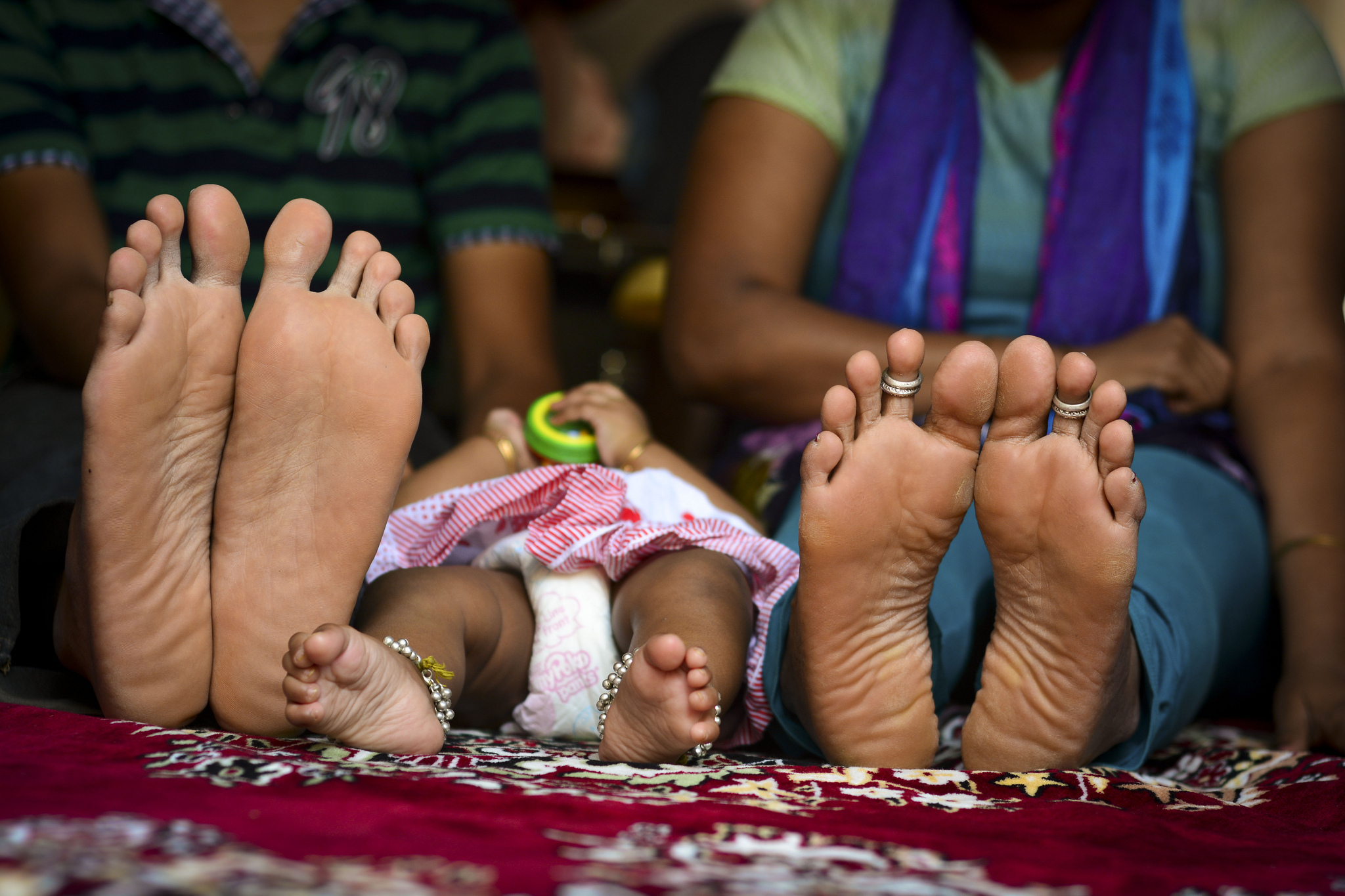 Image of a baby's feet in the middle of two adults' feet.