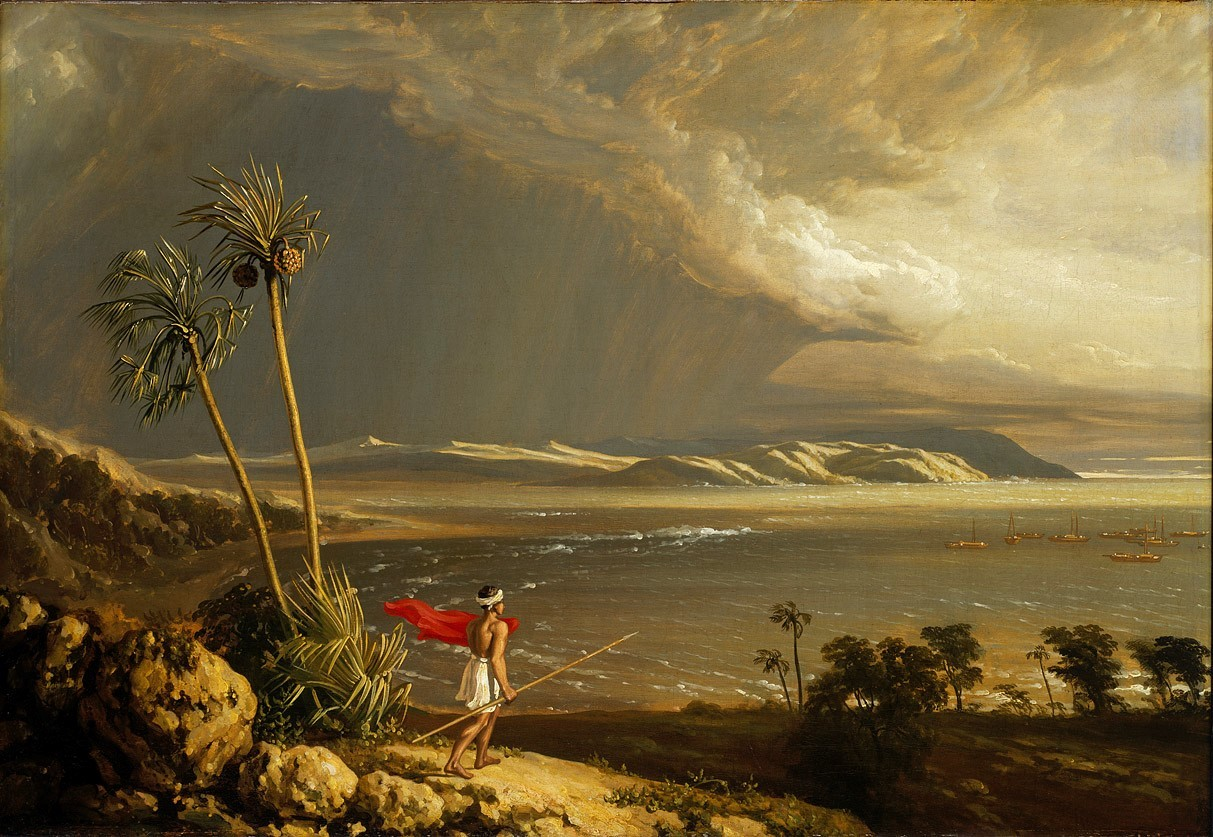 Indigenous figure with red cloak and spear, stands looking across a bay with palm trees and dramatic skyline. Boats are in the bay in the distance.