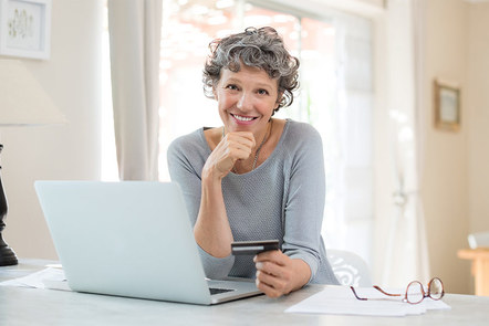 Mature woman using a laptop and holding a credit card.