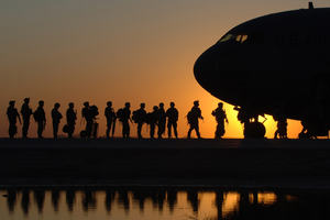 US army soldiers boarding a plane at sunrise