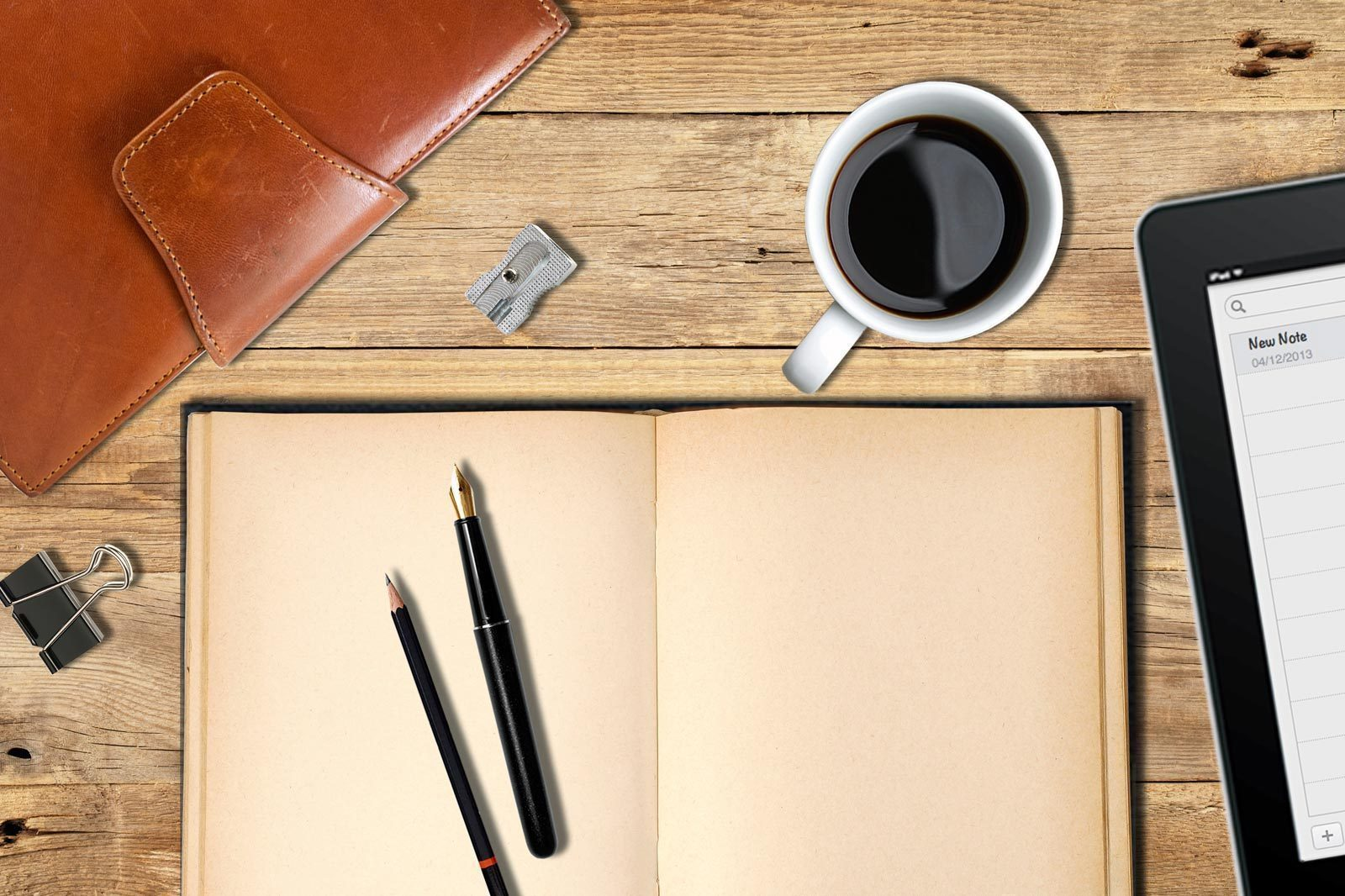 A pen and pencil sit on an open notebook with a coffee and an iPad close at hand, ready to start writing fiction