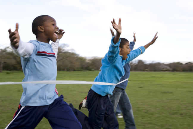 Group of young boys racing outdoors, running through the finishing tape with arms outstretched.