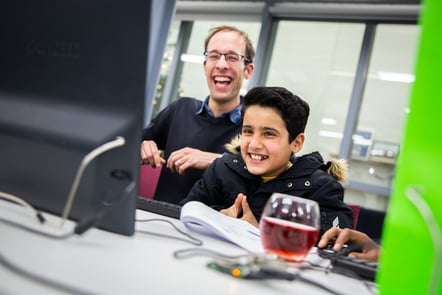 A child and a teacher, smiling at what they are seeing on a computer screen