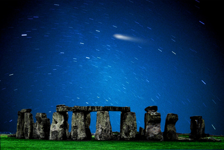 Photo of historic site of stone henge at night showing stars moving at speed across the sky