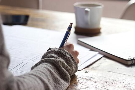 Woman making notes at table
