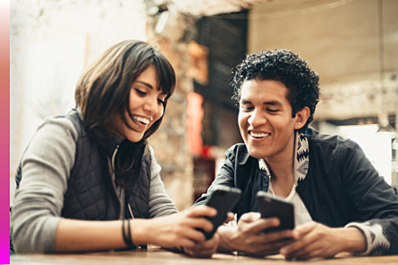 Man and woman smiling with their mobile phones in their hands