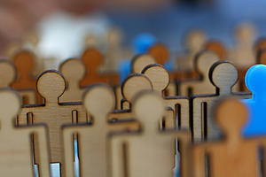 A collection of plain wooden figures with one blue figure clearly standing out from the crowd