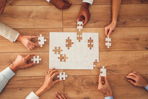 A white jigsaw puzzle with missing pieces being placed into it by a number of different hands. Each hand is holding on to one of the 6 missing pieces