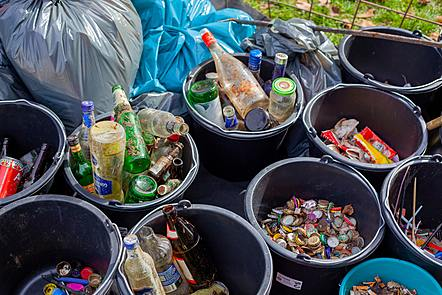 Several bins of rubbish sorted for recycling. Some contain bottles, others contain bottle tops or sweet wrappers