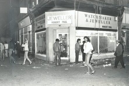 A photograph of a jewellery shop in Moss Side with smashed front windows. Young people walk past and look at the camera