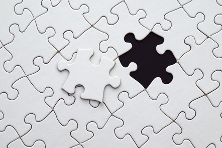 A puzzle with a missing puzzle piece. The missing puzzle piece about to be fitted