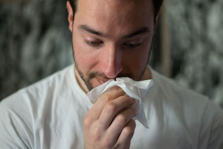 A mildly sick men wiping his nose with a tissue