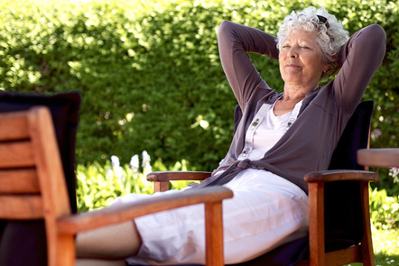 Senior citizen relaxing on a chair outside.