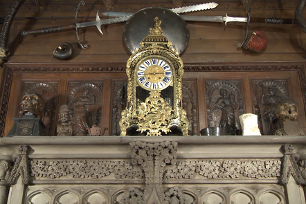 An array of objects on display including skulls, a golden clock and two crossing zweihander swords above the fireplace at Abbotsford.