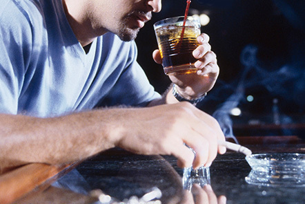 A man at a bar drinking alcohol and smoking a cigarette.