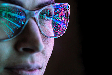 Close-up of a woman's face who's glasses are reflecting a computer screen.