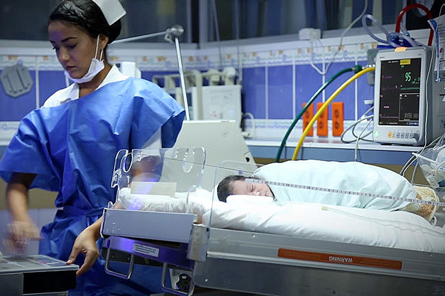 Nurse stands beside a sleeping baby in an open incubator