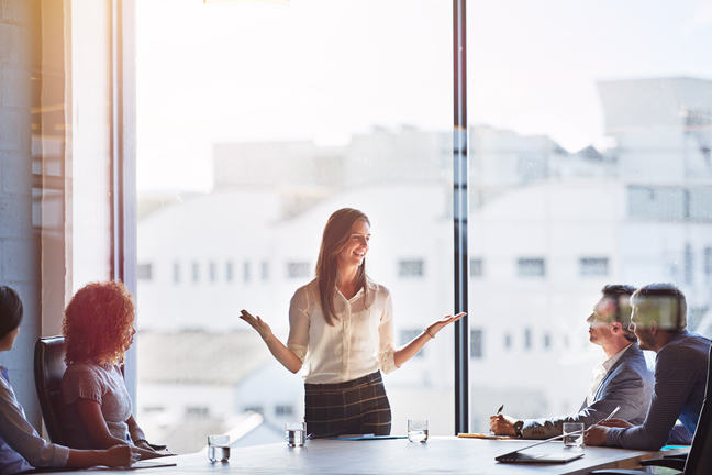 Woman standing up in meeting explaining her ideas