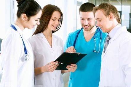A group of health care professionals studying a clipboard