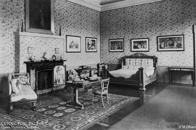Black and white photograph of Victoria's bedroom including a desk and bed.