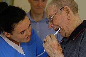 Carer helping clean an elderly man's teeth