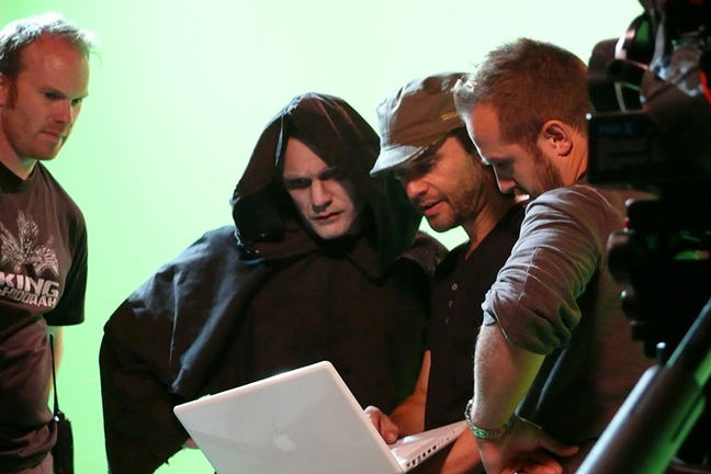 a bunch of crew and cast gather round a laptop on set