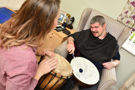 A young man is playing a drum with a stick smiling while a female music therapist is facing him playing a drum with her hands