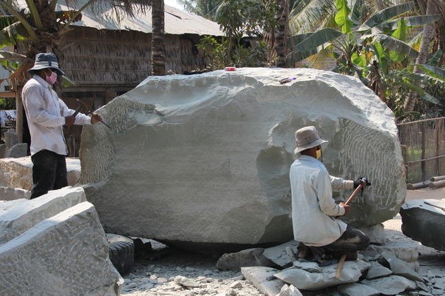 Two workers carving out a sandstone to make a sculpture
