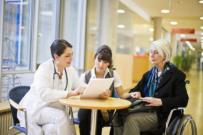 Female doctor discussing a care plan with an elderly female patient in a wheelchair and a younger woman