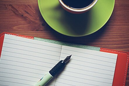 A fountain pen resting on an open notebook, next to a cup of coffee.