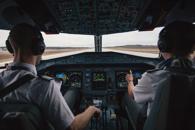 Two pilots sitting the cockpit of an aircraft