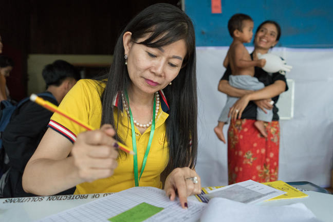 A female staff member sits with pen in hand, checking names off a list at a data collection centre.