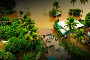 An aerial photograph of a flooded village in Kerala, India - villagers stand on a road cut off by water
